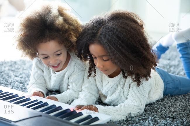 Ethnic sister girls playing piano on carpet at living room