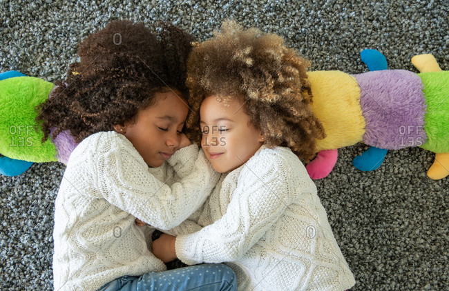 Ethnic sister girls nap on the gray carpet with happy dreams