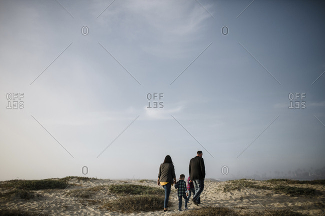 Rear view of parents with sons walking at beach against sky during sunny day