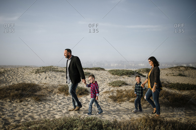 Side view of parents with sons walking at beach against sky during sunny day