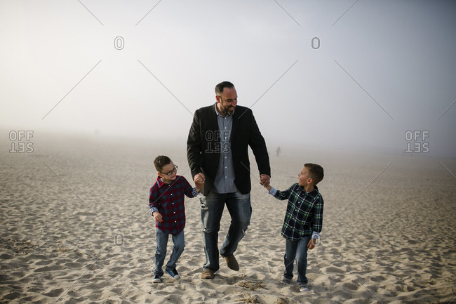 Smiling father with cute sons walking at beach against sky during foggy weather