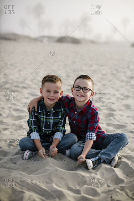 Portrait of smiling cute brothers sitting on sand at beach during foggy weather
