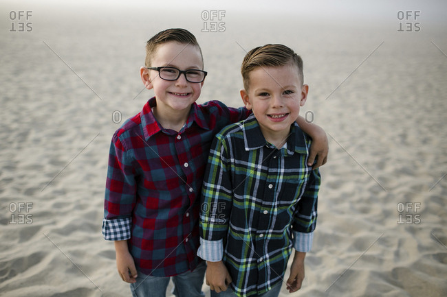 Portrait of smiling cute brothers standing on sand at beach during sunset