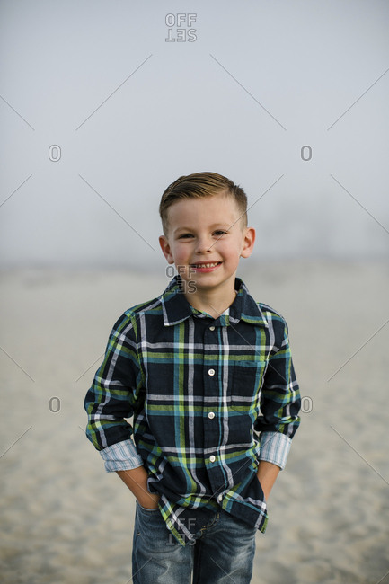 Portrait of cute boy with hands in pockets standing at beach against sky during foggy weather