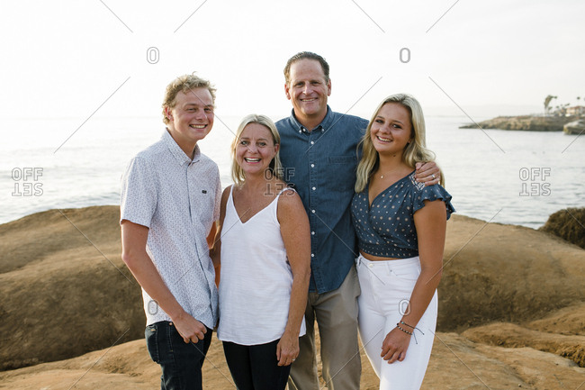 Portrait of cheerful family standing on cliff against sea during sunset