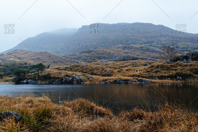 Scenic view of lake by mountain against cloudy sky during foggy weather