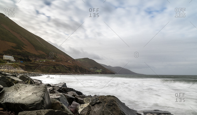 Scenic view of sea by mountains against cloudy sky at Ireland