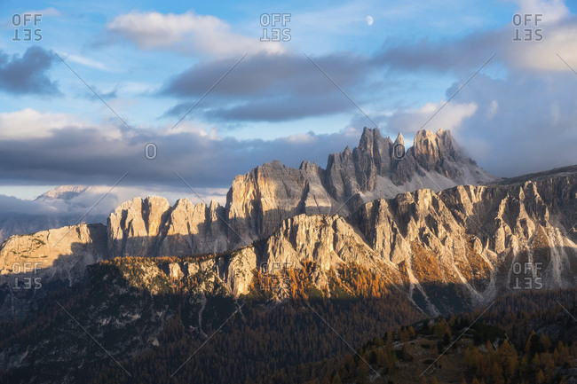 Scenic view of Dolomites against cloudy sky during sunset in forest