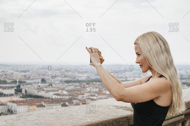 Side view of woman photographing cityscape with mobile phone while standing by retaining wall against cloudy sky