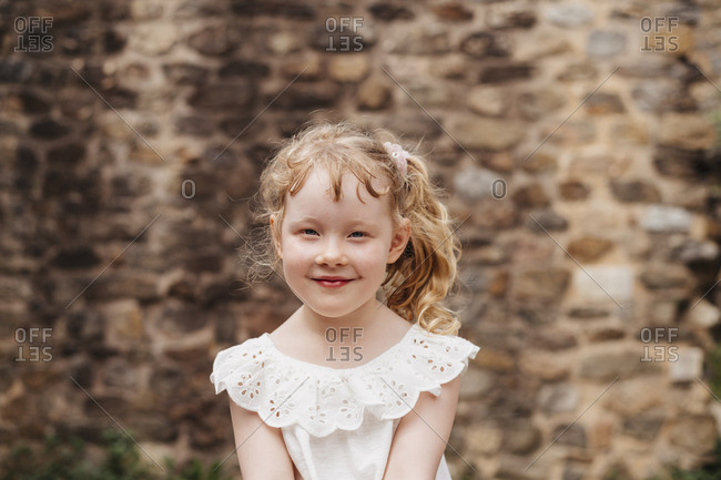 Portrait of cute smiling girl with blond hair sitting against old brick wall