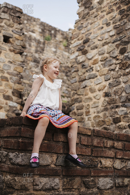 Low angle view of cute smiling girl with blond hair sitting against old brick wall