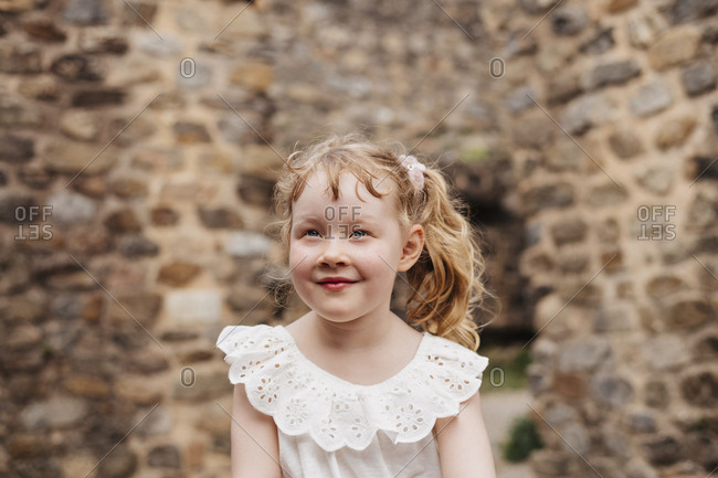 Cute smiling girl with blond hair looking away while sitting against old brick wall