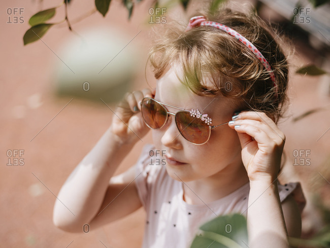 High angle view of cute girl wearing sunglasses while standing on footpath in city