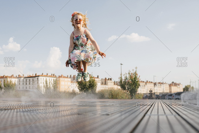 Full length of cute girl wearing sunglasses jumping on footpath against sky in city