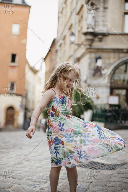 Happy cute girl spinning on street against buildings in city