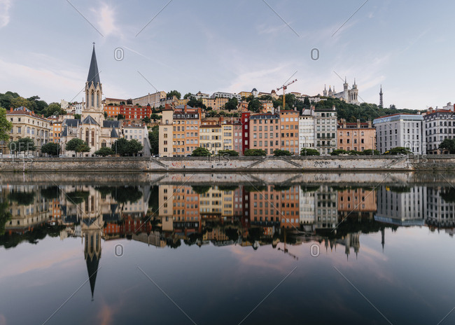Buildings reflecting on Saone river against sky in city during sunset