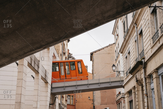 Low angle view of cable car moving on bridge amidst buildings in city