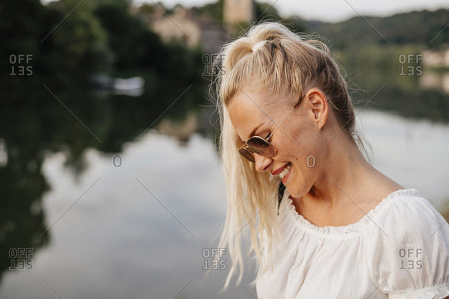 Smiling woman wearing sunglasses standing by Saone River during sunset