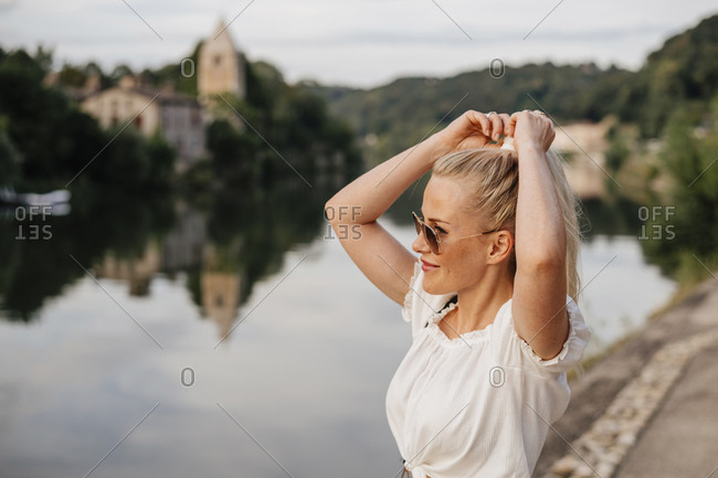 Smiling woman tying hair while standing by Saone River against sky during sunset