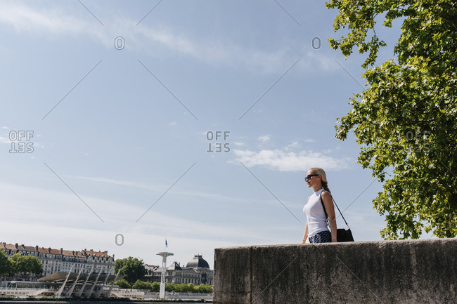 Low angle view of woman wearing sunglasses standing by retaining wall against sky in city during sunny day