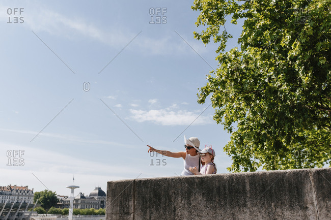 Low angle view of mother gesturing while standing with daughter against sky in city during sunny day