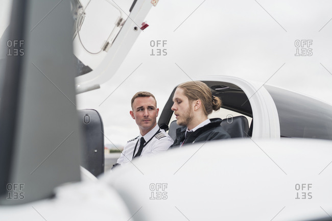 Male pilots talking while sitting in airplane against cloudy sky