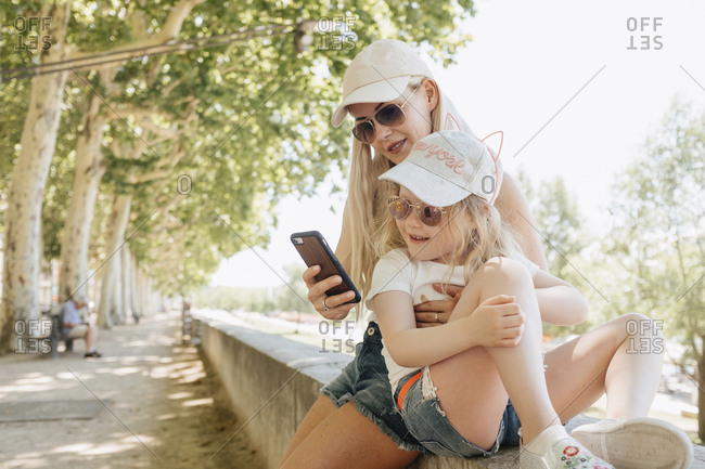 Mother using smart phone while sitting with daughter on retaining wall in park