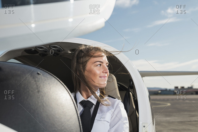 Smiling thoughtful female pilot looking away while sitting in airplane against sky at airport