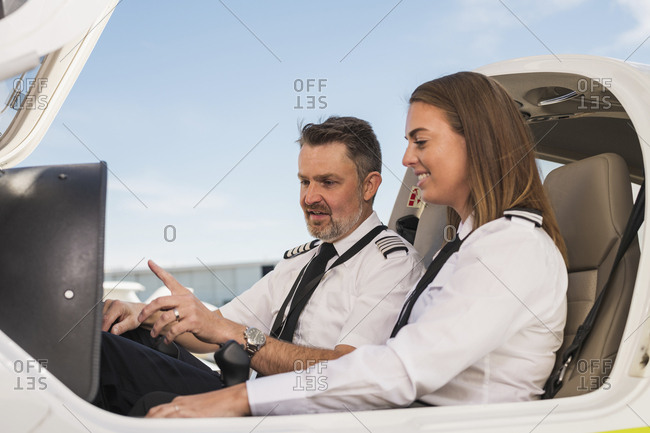 Male pilot teaching female trainee in airplane against blue sky at airport