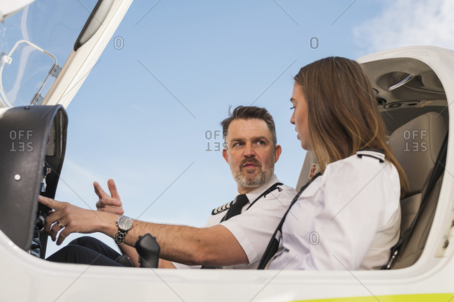 Low angle view of male pilot teaching trainee to operate control panel in airplane against blue sky at airport