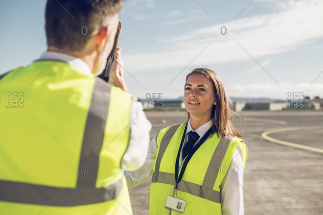 Rear view of male engineer showing airplane parts to female trainee while standing against blue sky on airport runway