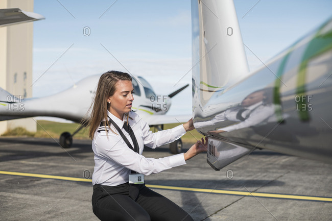 Female engineer examining airplane parts while crouching on airport runway against sky during sunny day