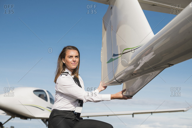 Side view of female engineer examining airplane parts while crouching on airport runway against blue sky during sunny day