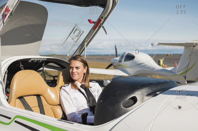 Smiling female pilot looking away while sitting in airplane against blue sky at airport during sunny day