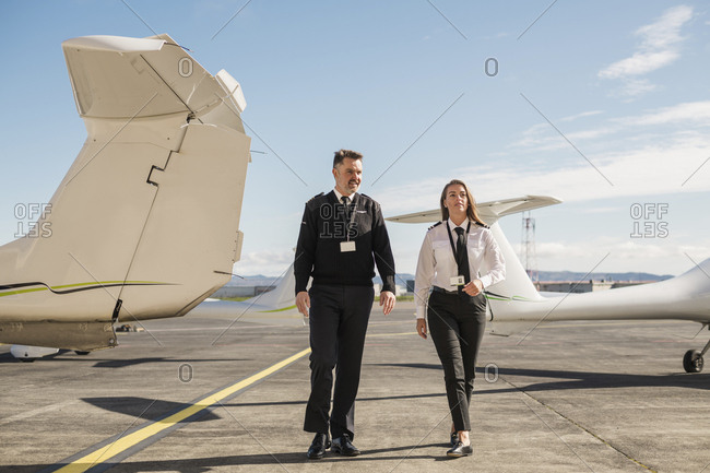Pilots talking while walking on airport runway against blue sky during sunny day