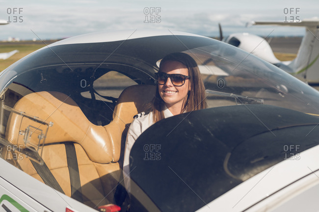 Smiling female pilot wearing sunglasses sitting in airplane seen through windshield