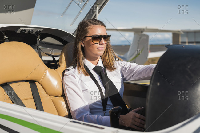 Confident female pilot wearing sunglasses sitting in airplane against blue sky during sunny day