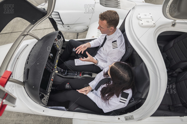 High angle view of male pilot guiding female trainee while sitting in airplane at airport runway