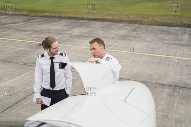 High angle view of engineer showing airplane parts to trainee while standing on airport runway