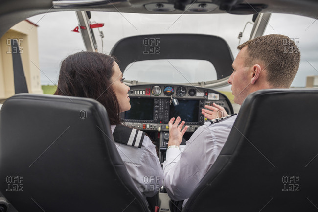 Rear view of male pilot giving training to female trainee while sitting in airplane at airport
