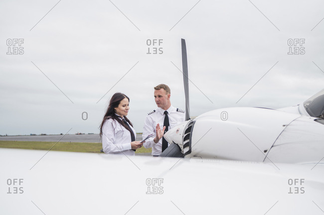 Engineer showing airplane parts to female trainee while standing against cloudy sky on airport runway