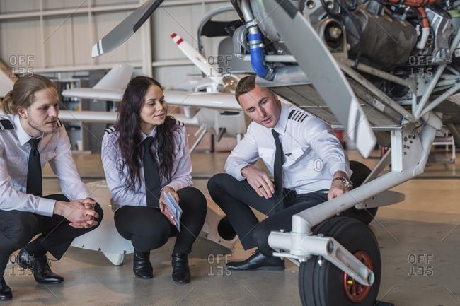 Engineer showing airplane wheel to trainees in hangar