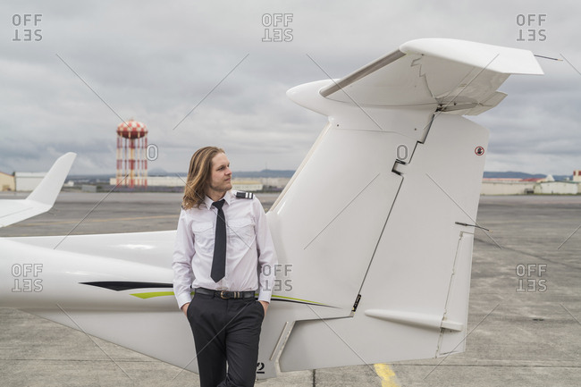 Confident male pilot with hands in pockets standing by airplane on airport runway against cloudy sky