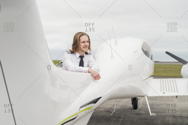 Smiling male pilot looking away while standing by airplane on airport runway against cloudy sky