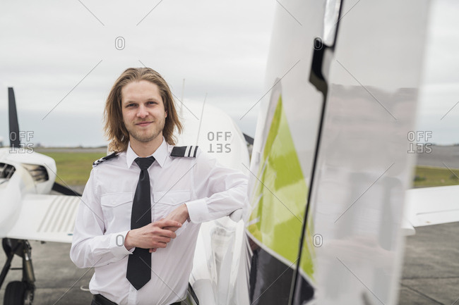 Portrait of confident male pilot standing by airplane against cloudy sky on airport runway