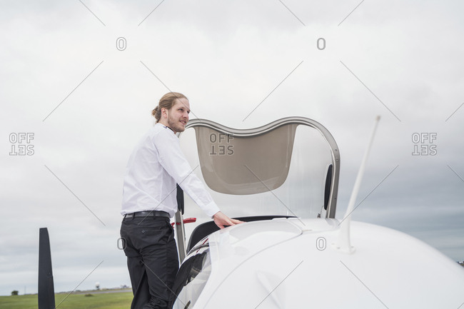 Side view of confident male pilot looking away while standing by airplane against cloudy sky