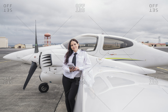 Portrait of confident female pilot standing by airplane against cloudy sky on airport runway