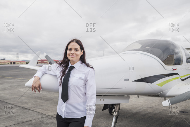 Portrait of smiling female pilot standing by airplane against cloudy sky on airport runway