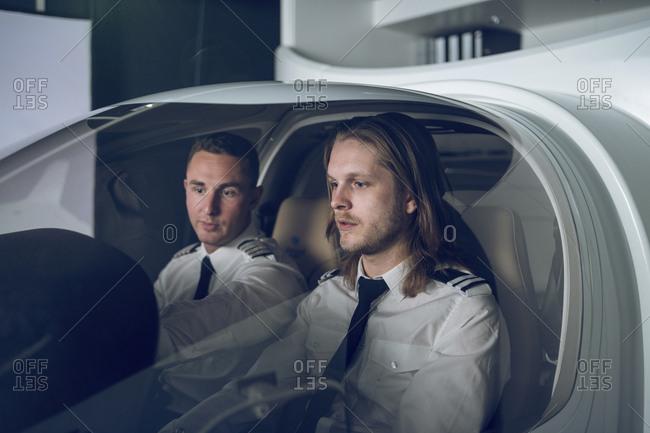 Male pilot guiding trainee in flight simulator