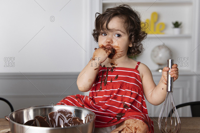 Messy baby girl eating chocolate while sitting on table against wall at home
